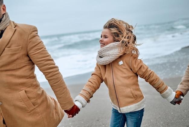 Immagine ritagliata di una giovane coppia sposata e della loro graziosa figlia che si divertono sulla spiaggia in inverno indossando vestiti caldi e sciarpe nella stagione fredda.