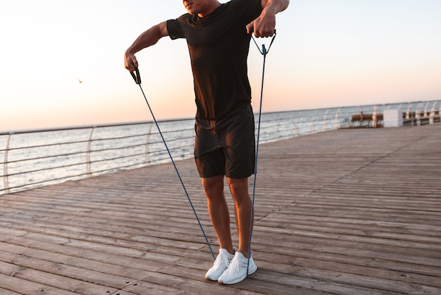 Immagine ritagliata di un giovane sportivo che fa esercizi