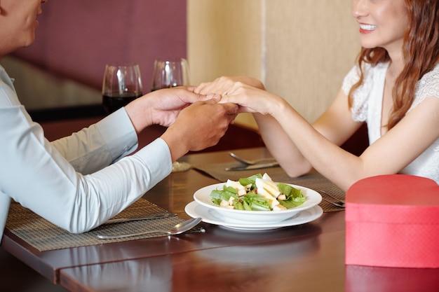 Immagine ritagliata di una giovane donna che tiene per mano la fidanzata e le dice complimenti e parole d'amore quando sono seduti al tavolo del ristorante