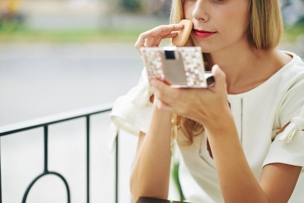 Immagine ritagliata della giovane donna che guarda lo specchio compatto e l'applicazione di cipria