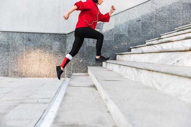 Immagine ritagliata di una giovane sportiva che corre su per le scale all'aperto
