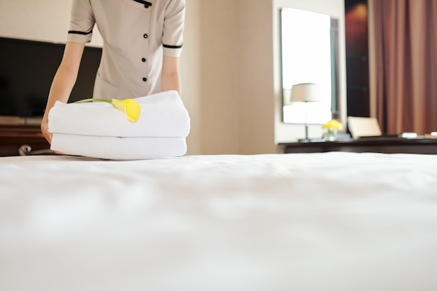 Mago ritagliato della cameriera che mette un asciugamano fresco e una calla sul letto quando prepara la stanza per i nuovi ospiti