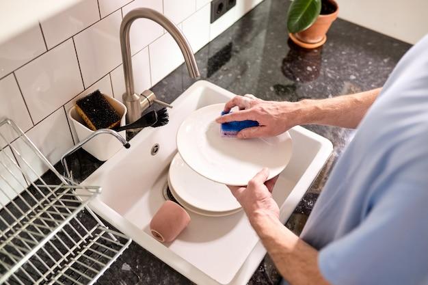 Mani maschili tagliate che lavano i piatti al lavello della cucina mentre fanno le pulizie a casa nei fine settimana vista dall'alto