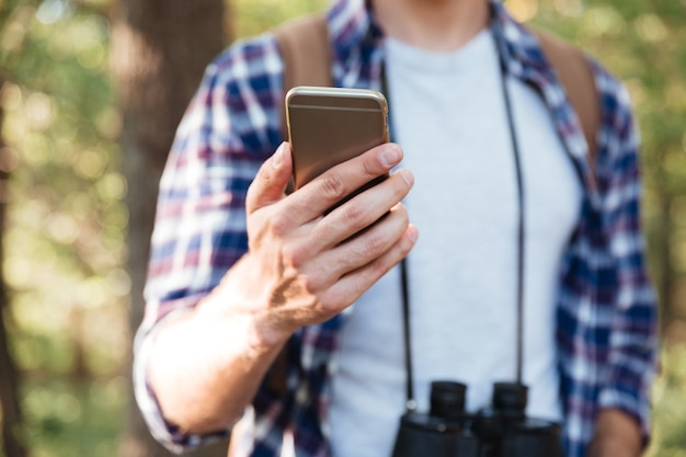 Ritagliato di uomo con telefono nella foresta