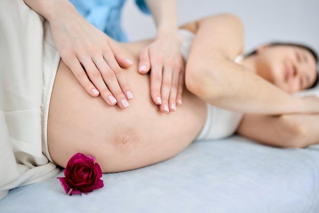 Massaggiatore ritagliato che fa massaggio alla donna incinta sdraiata sul letto