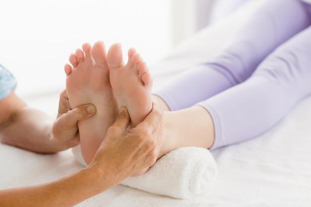 Massaggiatore ritagliato che dà massaggio ai piedi alla donna