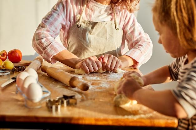 La madre ritagliata insegna alla figlia a stendere la pasta per preparare gustosi biscotti, biscotti a casa. concetto di panetteria