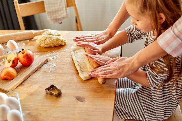 La mamma ritagliata insegna alla figlia a fare il lavoro con la pasta usa il perno del rullo in cucina, la madre caucasica che cucina i panini o la torta con la piccola ragazza del bambino in età prescolare. vista dall'alto