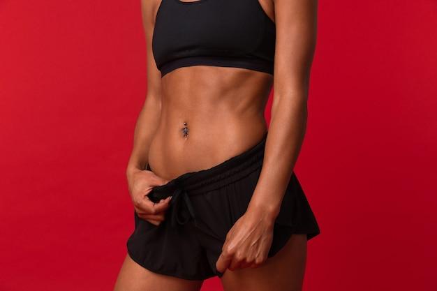 Foto ritagliata della donna afroamericana in abiti sportivi neri in piedi, isolata sopra la parete rossa