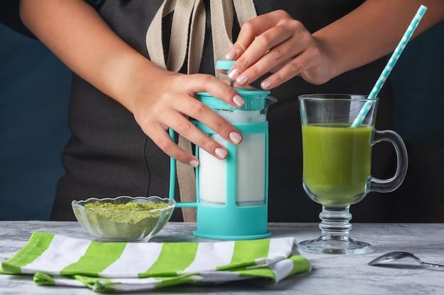 Foto ritagliata di una ragazza barista. latte a base di tè verde matcha e primo piano di latte di soia. prodotto vegetariano.