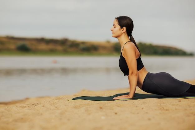 Foto ritagliata della ragazza che pratica yoga, posa del cobra sulla sabbia.