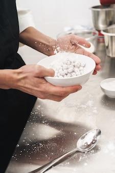 Foto ritagliata di un bel giovane cuoco chef in cucina che cucina al chiuso.