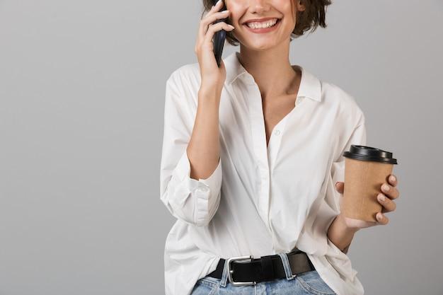 Foto ritagliata di felice giovane donna d'affari parlando da telefono cellulare bere caffè