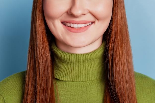 Foto ritagliata di una giovane donna gioiosa con un sorriso raggiante isolato su sfondo blu