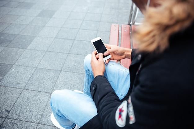 Foto ritagliata dell'uomo che tiene il cellulare in mano e chiacchiera mentre ascolta musica all'aperto.