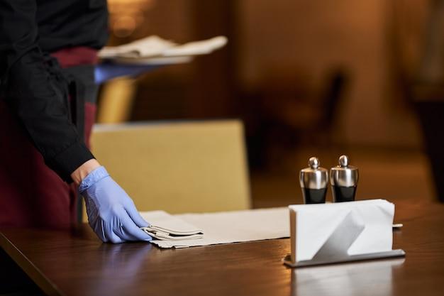 Foto ritagliata della cameriera che usa guanti usa e getta mentre prepara il tavolo per s