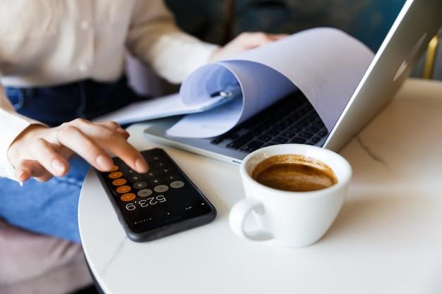 Foto ritagliata della giovane donna seduta in un caffè al chiuso lavora con il computer portatile che tiene i documenti utilizzando il telefono cellulare