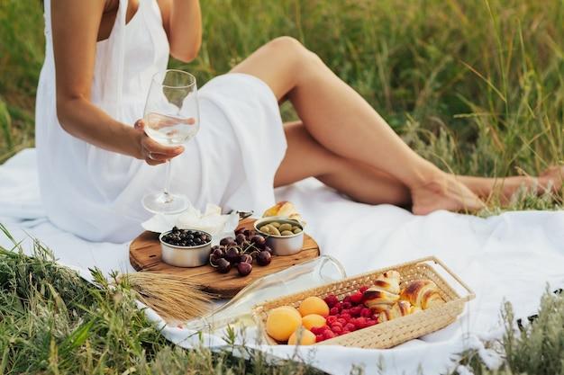 L'immagine ritagliata della donna sta facendo un picnic su un prato nel parco con vino, formaggio e frutta fresca.