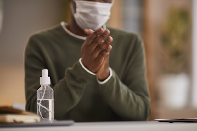 Ritagliata ritratto di uomo afro-americano che igienizza le mani sul posto di lavoro con focus sulla bottiglia spray in primo piano, copia dello spazio
