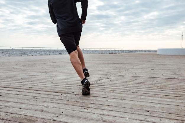 Ritagliato ritratto di uomo fitness vista posteriore vicino al mare