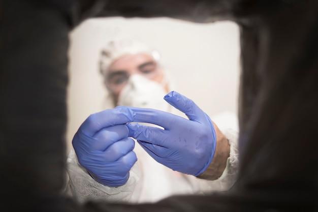 Ritratto ritagliato, professionista sanitario che butta via i guanti in lattice monouso blu nella spazzatura. protocollo di controllo delle infezioni.
