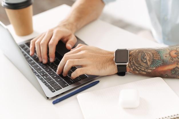 Ritratto ritagliato di un uomo con un tatuaggio che utilizza un computer portatile seduto al tavolo in ufficio