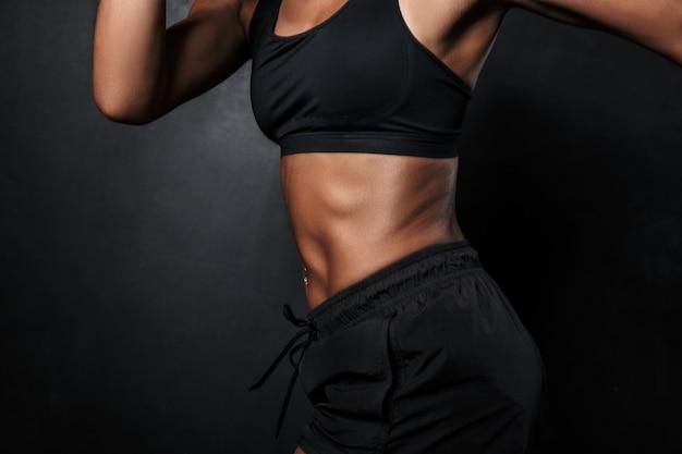 Ritagliato ritratto di muscolosa donna afroamericana in abbigliamento sportivo e involucri a mano in esecuzione isolato su nero