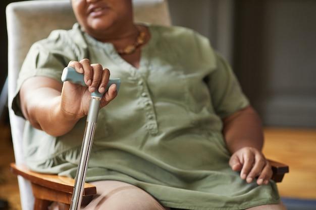 Ritratto ritagliato di una donna afroamericana anziana che tiene la canna nello spazio della copia della casa di cura
