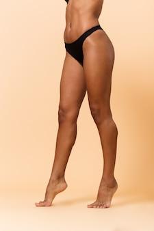 Ritagliata ritratto di donna magra 20s indossa lingerie nera, in piedi isolato sopra il muro beige
