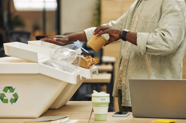 Ritagliata ritratto di irriconoscibile uomo afro-americano che mette il bicchiere di carta nel cestino della raccolta differenziata in ufficio, copia dello spazio