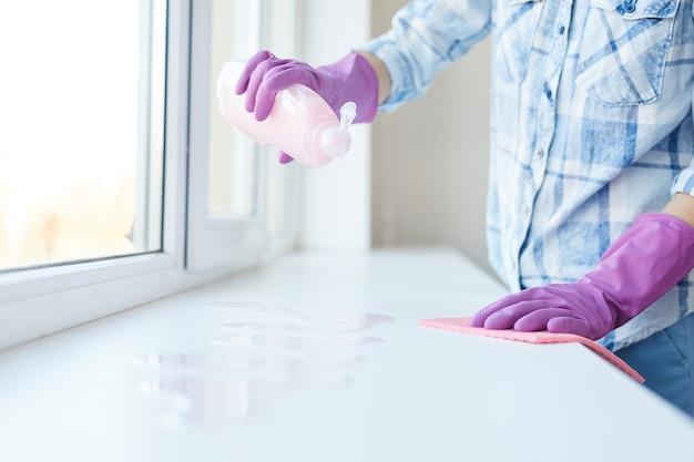 Ritagliata ritratto di donna irriconoscibile lavare i vetri durante le pulizie di primavera, concentrarsi sulle mani femminili che indossano guanti rosa
