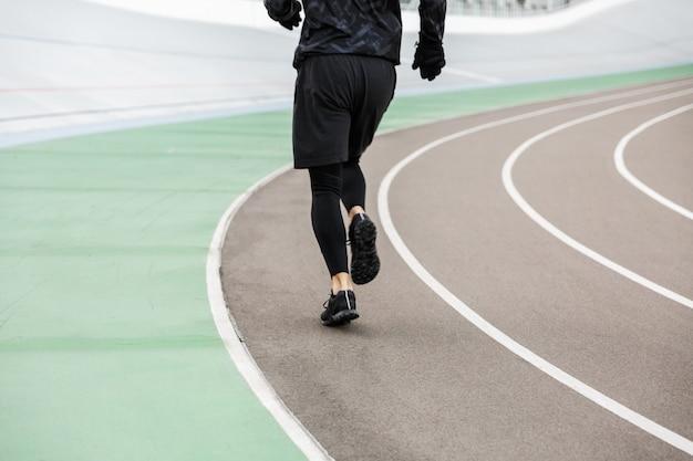Ritratto ritagliato delle gambe di un giovane sportivo in forma che corrono in pista allo stadio all'aperto