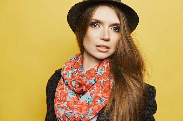 Ritagliato ritratto di giovane donna con trucco delicato nel cappotto con stampa leopardata, cappello alla moda e sciarpa colorata. copia spazio per il testo.
