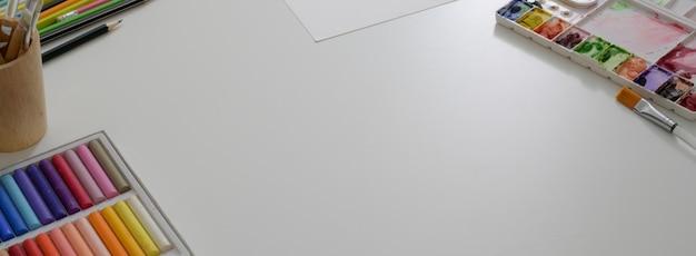Ritagliata area di lavoro dell'artista con carta da schizzo, pastelli ad olio, strumenti di pittura e copia spazio