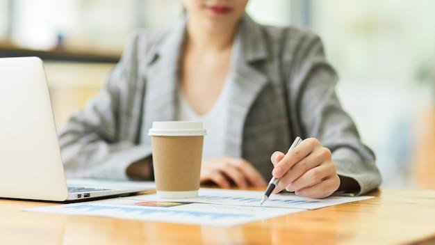 Ritagliata scatto di una bellissima giovane donna d'affari che fa alcune scartoffie mentre è seduta alla scrivania dell'ufficio davanti al computer portatile.