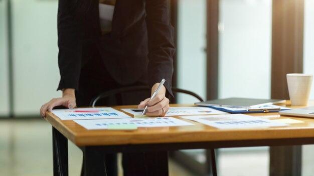 Colpo ritagliato di donna d'affari che lavora in ufficio scrivere su documenti che analizzano il budget di gestione fiscale