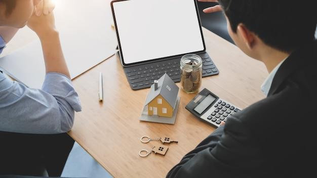 Ritagliata foto di uomini d'affari di consulenza sull'interesse a investire nel settore immobiliare