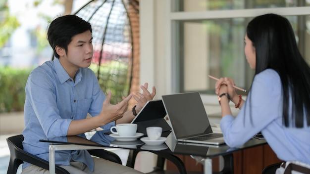 Colpo potato delle persone di affari che discutono sul loro lavoro con il computer portatile