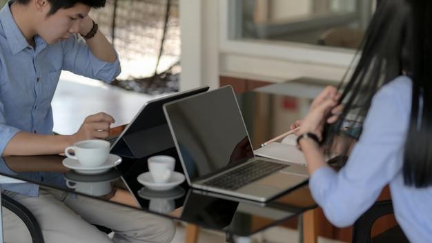 Colpo ritagliato di uomini d'affari, concentrandosi sul loro lavoro con il computer portatile