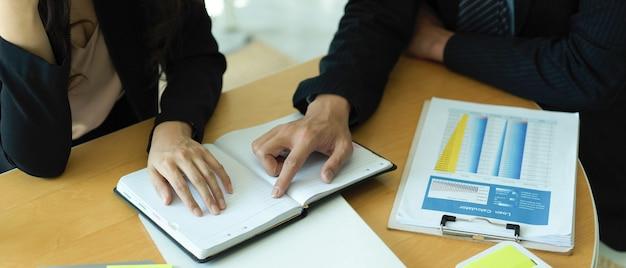 Ritagliata colpo di mani di uomini d'affari che punta sul taccuino in bianco durante la consultazione sul loro progetto