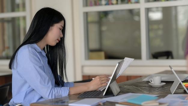 Colpo potato della donna di affari che si concentra sul suo lavoro nello spazio semplice di lavoro in comune