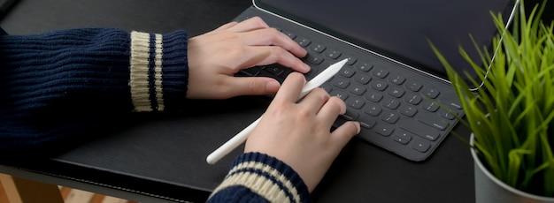 Colpo potato della donna di affari che scrive sulla compressa digitale sulla tavola nera