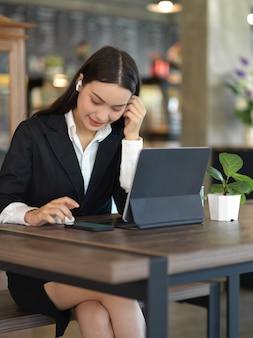 Ritagliata colpo di imprenditrice con auricolare wireless rilassante con lo smartphone mentre si lavora con il tablet