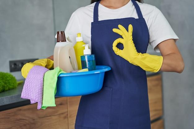 Colpo ritagliato della donna delle pulizie che mostra il segno ok mentre tiene in mano un contenitore pieno di prodotti e attrezzature per la pulizia, in piedi nella cucina moderna. lavori domestici e pulizie, concetto di servizio di pulizia