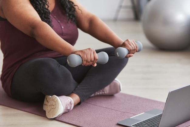 Ritagliata foto di una donna formosa afroamericana che si allena a casa con manubri mentre è seduta su un tappetino da yoga e guarda video di allenamento online, copia spazio