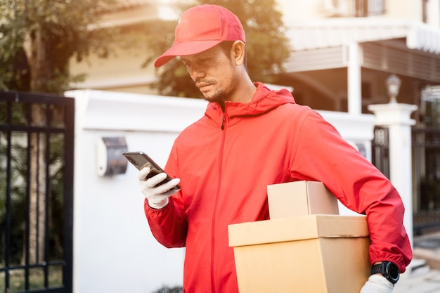 Colpo ritagliato di un fattorino in uniforme rossa tiene i pacchi postali in strada guarda il cellulare che controlla l'indirizzo gps per consegnare le cose al cliente. servizio di consegna durante la pandemia di covid-19.