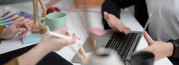 Colpo ritagliato del team di designer consulenza sul loro progetto con laptop, tablet digitale e forniture di design