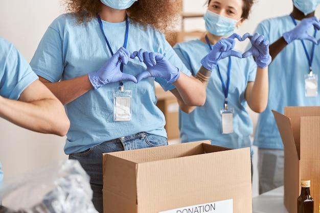 Scatto ritagliato di diverse persone che indossano maschere protettive uniformi blu e guanti che mostrano il cuore dell'amore
