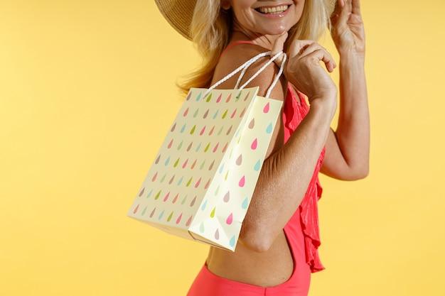 Ritagliata foto di una donna alla moda eccitata in costume da bagno rosso e cappello di paglia che sorride mentre posa con