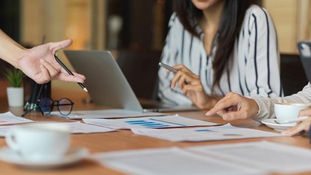 Scatto ritagliato del team aziendale femminile che discute insieme il proprio progetto nella sala riunioni